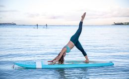Athletic young woman in SUP Yoga practice side bend leg lift Pose in Ala Moana Hawaii. Young woman in SUP Yoga practice side bend leg lift Pose in Ala Moana stock images
