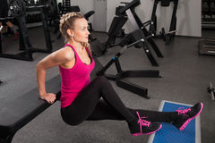 Athletic young woman training on exerciser Stock Images