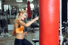 Athletic young woman training with punching bag at gym Stock Photography