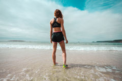 Athletic young woman walking on the beach Stock Photo