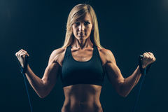 Athletic young woman working on biceps with Stock Photos