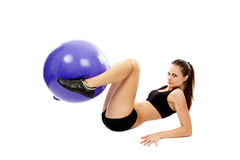 Athletic young woman working out abs and legs with the fitball Royalty Free Stock Image