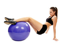 Athletic young woman working out abs and legs with the fitball Stock Image
