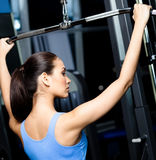 Athletic young woman works out on gym equipment Royalty Free Stock Photos