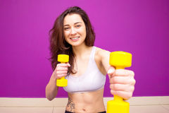 Athletic young woman works out with pink dumbbells Royalty Free Stock Image