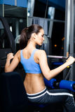 Athletic young woman works out on training apparatus Royalty Free Stock Image