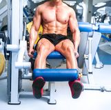 Athletically built sportsman in the gym Stock Photography