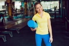 athletics Atleta fêmea novo com uma esteira para esticar nas mãos imagens de stock