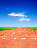 Athletics track. An empty red athletics track in a green field under a blue sky Stock Photos