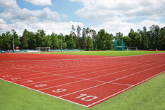 Athletics track. An empty red athletics track in a green field under a blue sky Stock Photography