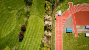 Athletics track and golf course. Abstract aerial view looking down onto an athletics running track set against the green of a neighbouring golf course Stock Photo