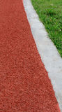 Athletics Track Lane  and grass. Athletics Track Lane made with orange rubber Stock Photography
