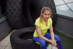 Athletics, after training with tyre. Smiling young female sportswoman sitting on a tire Royalty Free Stock Photos