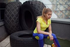 Athletics, after training with tyre. Smiling young female sportswoman sitting on a tire Royalty Free Stock Photography