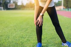 Athletics women runner hand touching and having a knee pain and injury after running outdoor. Athletics woman runner hand touching and having a knee pain and royalty free stock photography