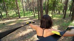Athletisch, Frau, Trainer, Lehrer, führt durch und tut trainiert mit Eignung trx System, TRX-Traggurte In der Kiefer stock video