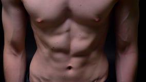 Athletische ABS und Torso des starken Mannes mit den belasteten Muskeln auf backgroung im Studio stock footage