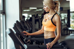 Athletische blonde Frau, die auf Tretmühle an der Turnhalle läuft Stockfoto