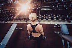 Athletische Bodybuilderfrau mit Dummköpfen schönes blondes Mädchen mit den Muskeln Gymnastik Lizenzfreies Stockfoto