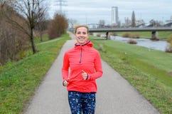 Athletische erwachsene Frau, die entlang dem Graben rüttelt Lizenzfreies Stockfoto