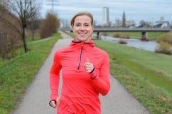 Athletische erwachsene Frau, die entlang dem Graben rüttelt Stockfotografie