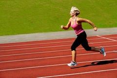 Athletische Frau, die auf Bahn läuft Lizenzfreie Stockfotos