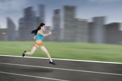 Athletische Frau, die auf Bahn läuft Stockfotos