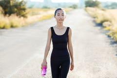 Athletische Frau, die auf Landstraße- und Tragenwasser Flasche geht Stockfoto