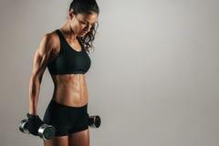 Athletische Frau, die bei den Gewichten an ihren Seiten liegt Lizenzfreie Stockbilder