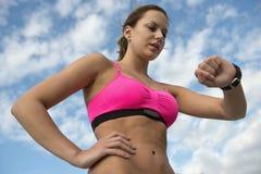 Athletische Frau, die Herzfrequenzmonitor verwendet Stockfoto