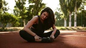 Athletische Frau, die ihre Kniesehne, Beinübungs-Trainingseignung vor Training draußen auf dem Stadion am Sommer ausdehnt stock video
