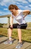 Athletische Frau, die ihre Rückenmuskulatur durch Verletzung berührt Lizenzfreies Stockbild