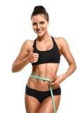 Athletische Frau, die ihre Taille misst und Daumen hohes Isolat zeigt Stockfotografie