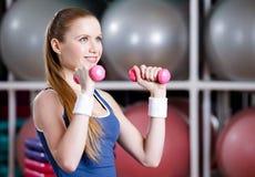 Athletische Frau, die mit Dummköpfen ausarbeitet Stockfotografie