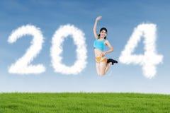 Athletische Frau, die mit geformten Wolken von 2014 springt Stockbild