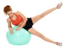 Athletische Frau, die mit Turnhallenball trainiert Stockbild