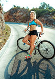 Athletische Frau, die nahe ihrem Fahrrad auf einer Gebirgsstraße steht Stockfotos
