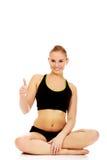 Athletische Frau, die oben queresmit beinen versehenes auf dem Boden und dem Showdaumen sitzt Lizenzfreie Stockfotografie