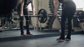 Athletische Frau führt rumänisches deadlift mit einem Barbell in einer Turnhalle durch
