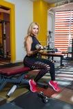 Athletische Frau nimmt an einer Turnhalle mit Dummköpfen auf der Bank für das Drücken der Muskeln der Hände teil Stockfotos