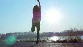 Athletische Frau strebt herein Sport auf der Flussbank bei Sonnenaufgang an Langsame Bewegung stock video