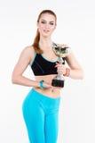 Athletische Frauenhaltungen mit der Meisterschaftstrophäe Lizenzfreies Stockfoto