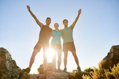 Athletische Freunde, die triumphierend zusammen auf einem Berg aufwerfen lizenzfreies stockfoto