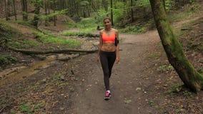 Athletische gebräunte Frau geht ruhig entlang Forest Road, gekleidet für das Rütteln stock footage