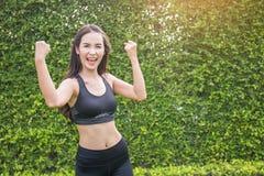 Athletische junge asiatische Frau, die Bizeps zeigt Stockfotos