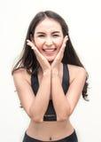 Athletische junge asiatische Frau, die mit ihren Händen halten ihr Gesicht lächelt Lizenzfreie Stockfotos