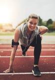 Athletische junge Blondine, die Kamera beim Ausdehnen betrachten Stockbild