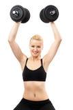 Athletische junge Dame, die mit Gewichten ausarbeitet Stockfotografie