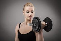 Athletische junge Dame, die mit Gewichten ausarbeitet Stockfotos