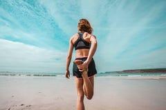 Athletische junge Frau, die auf den Strand ausdehnt stockfotos